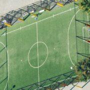 Een luchtfoto van een voetbalveld midden in de stad voor jongeren. Het veld is leeg