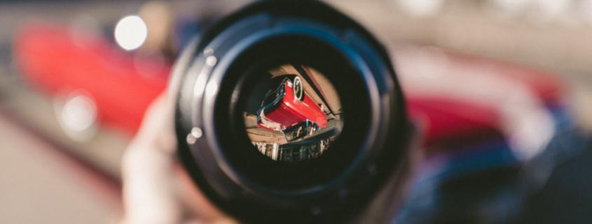 De lens van een camera is vol in beeld. Het beeld zelf is geblurd. Er is in het midden van de lens een foto te zien van een rode auto op zijn kop
