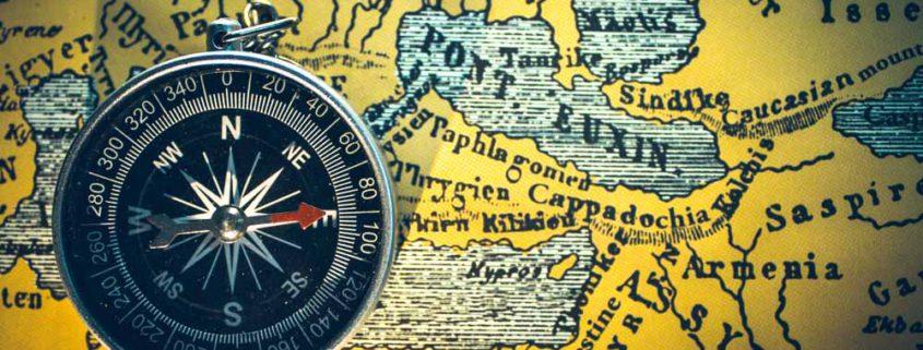 Een kompas wijst naar het oosten en ligt op een oude land kaart van klein-Azie