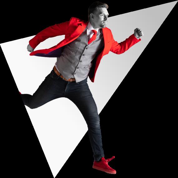 Renaldo springt uit een driehoek in een rood NOBLY pak   NOBLY Authentieke Communicatie & Creatie