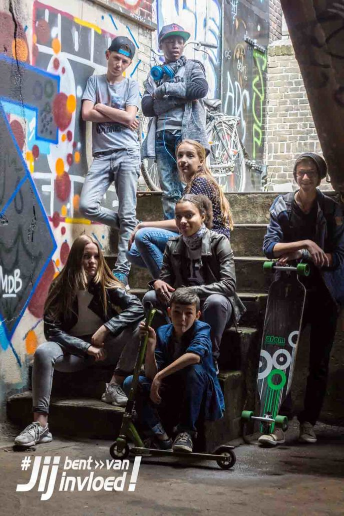 A group of teenagers hang out and sit on the stairs next to a wall of graffiti