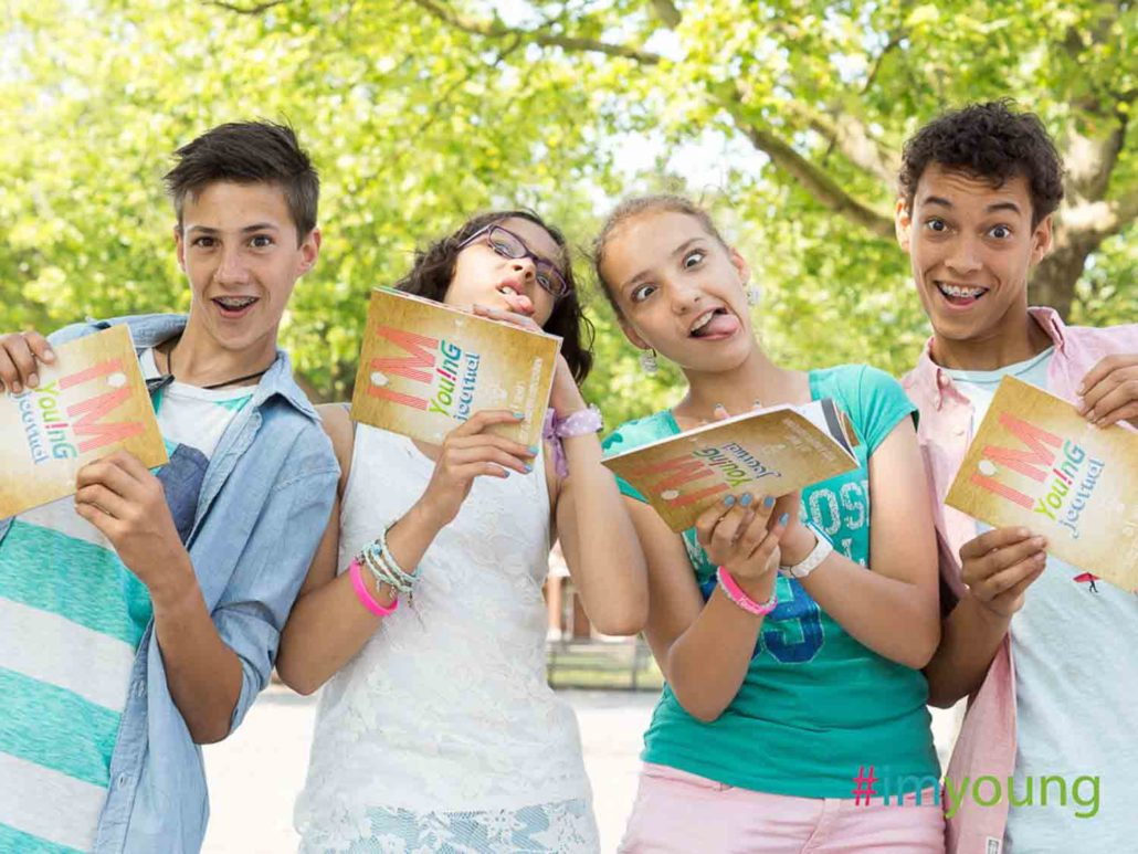 A group of teenagers is holding the I'm You!nG journal