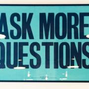 Op een witte wand hangen 2 klokken en 1 quote. Op de quote staan ASK MORE QUESTIONS